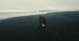 Back aerial view of the young couple walking on the black volcanic beach in Iceland. Romantic date near the sea. stock video
