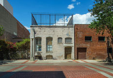 Back Alley Brick Walls. Vintage century-old worn brick walls of buildings as seen from back alley.  Arched windows, some barred, some grated. Past signs show Royalty Free Stock Images
