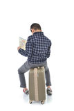Back of Asian boy sitting on lugguage and holding map on white background Royalty Free Stock Photography