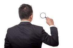 Back of Asian businessman with magnifying glass in his hand Royalty Free Stock Images