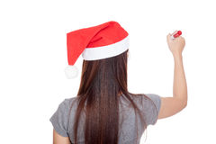Back of Asian girl with red santa hat write in the air Stock Photography