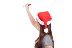 Back of Asian girl with red santa hat write in the air Stock Images