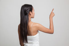 Back of Asian woman touching the screen with her finger. Royalty Free Stock Photo