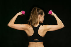 Back of athletic woman doing sport, lifting weights Royalty Free Stock Image