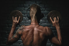 Back of athletic young aesthetic man listening music Royalty Free Stock Photo