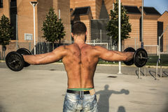 Back of Attractive Muscular Hunk Man Lifting Weights Outdoor Stock Image