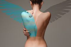 The back of attractive woman with angel wings on gray Royalty Free Stock Photography