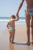 Back baby holding mother hand at shore Royalty Free Stock Images