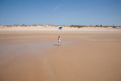 Back baby running to parasol beach Stock Image
