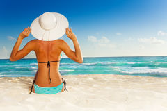 Back of beautiful girl sitting on beach. In striped swimwear and white hat Stock Images