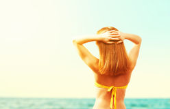 Back of beautiful happy woman in yellow swimsuit on the beach in Royalty Free Stock Image