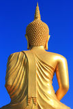 Back of a big golden Buddha. Statue on blue sky Royalty Free Stock Photo