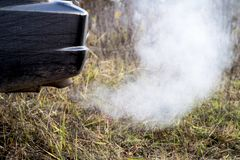 The back of the black car with the emission of smoke from the exhaust pipe on the background of nature. The concept of environmental pollution by vehicles royalty free stock photos