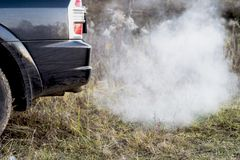 The back of the black car with the emission of smoke from the exhaust pipe on the background of nature. The concept of environmental pollution by vehicles stock photos