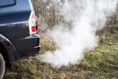 The back of the black car with the emission of smoke from the exhaust pipe on the background of nature. The concept of environmental pollution by vehicles royalty free stock photography