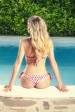 Back blonde young woman in swimsuit bikini. Poolside Stock Image