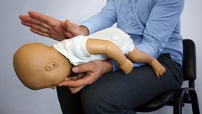 Back blows the Heimlich maneuver or Heimlich manoeuvre on a simulation mannequin infant dummy during medical training Basic Life. Support royalty free stock images