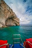 Tourist boat leaving Blue Caves in Zante. Back of a blue tourist boat sailing away from the Blue Caves, Zante Island, Greece stock images