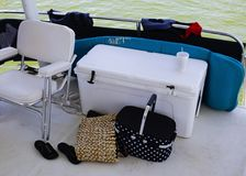 The back of the boat - Chair and cooler and picnic basket and be stock photo