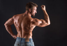 Back of bodybuilder man. Handsome bodybuilder man showing his mascular back and biceps. Strong man posing for photographer isolated on black background Royalty Free Stock Photos