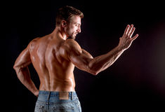 Back of bodybuilder man. Bodybuilder man showing his palm isolated on black in photo studio. Short-haired man demonstrating mascular back Stock Photos