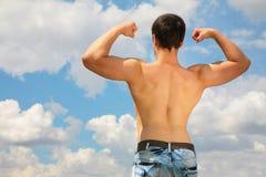Back bodybuilder on sky royalty free stock photo
