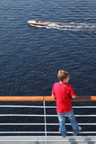 Back of boy standing at railing on deck of ship Stock Photos