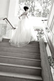 Back of bride. Black and white image of a bride up the upstairs.Bride ready for church in a soft blur.Shot from back view Royalty Free Stock Photos