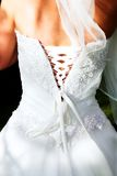 Back of the bride in beaded corset - outdoors. Ivory silk and chiffon wedding dress beaded with pearls ? view from the back Royalty Free Stock Image
