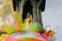 The back of buddha sculpture on pedestal. The pedestal is arounded by colorful material, Thailand Stock Images