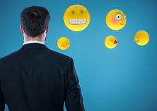 Back of business man with emojis against blue background. Digital composite of Back of business man with emojis against blue background Royalty Free Stock Photography