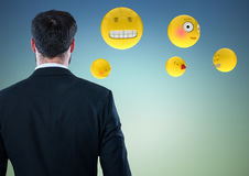 Back of business man with emojis against blue green background. Digital composite of Back of business man with emojis against blue green background Stock Photo