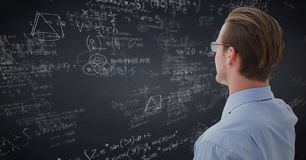Back of business man looking at navy chalkboard with math doodles. Digital composite of Back of business man looking at navy chalkboard with math doodles Royalty Free Stock Images