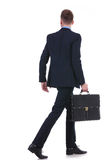 Back of a business man with suitcase walking away royalty free stock images