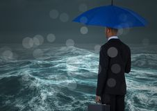 Back of business man with umbrella against stormy sea with bokeh Stock Photo