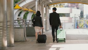 Back of business people drag baggage and walking on bridge. Behind of two young business people are dragging the luggage and walking on bridge Stock Image