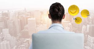 Back of business woman in chair with emojis against blurry skyline. Digital composite of Back of business woman in chair with emojis against blurry skyline Stock Image
