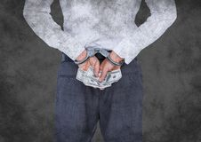 Back of business woman in handcuffs with money against grey grunge background Royalty Free Stock Images