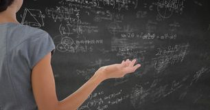 Back of business woman looking at grey wall with math doodles Royalty Free Stock Images