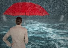 Back of business woman with umbrella against stormy sea with rain Royalty Free Stock Images