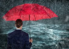 Back of business woman with umbrella in rain against stormy sea Royalty Free Stock Photo