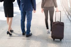 Back of businessman and businesswoman walk together with luggage on the public street,. Business travel concept stock photo