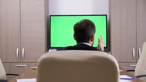 Back of businessman head talking to a green screen TV
