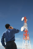 Back of businessman on phone and antenna Royalty Free Stock Photos