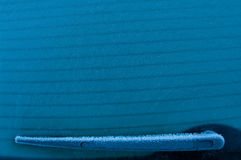 Back of the car wiper in winter. Winter frozen back car window, texture freezing ice glass background. Wiper covered with frost particles, copyspace, blue tone Stock Image