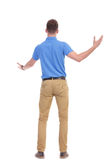 Back of casual young man welcoming someone Royalty Free Stock Photos