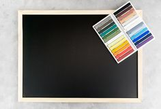 Back chalkboard mockup with colorful chalks on grey background. Business, interior design, lettering concept. Text space Stock Photo
