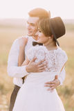 The back close-up portrait of the hugging newlyweds in the sunny field. The couple is dressed in the vintage style. Stock Images