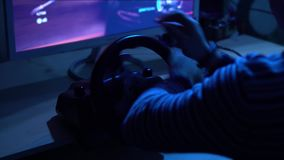 Back close-up shot of a man playing car racing video game using steering wheel stock video