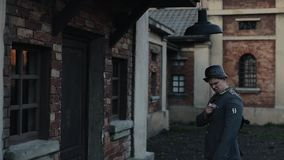 A rear close-up of a German soldier changing a bulb in a street lamp hanging over a door in an ancient red brick. A back close view of a German soldier in a stock video